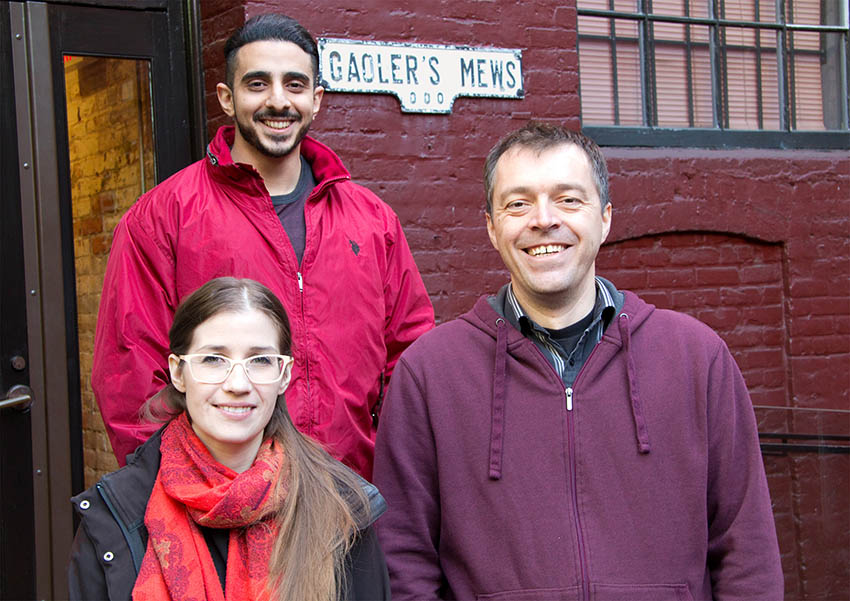 Three new OXD employees standing outside of the office
