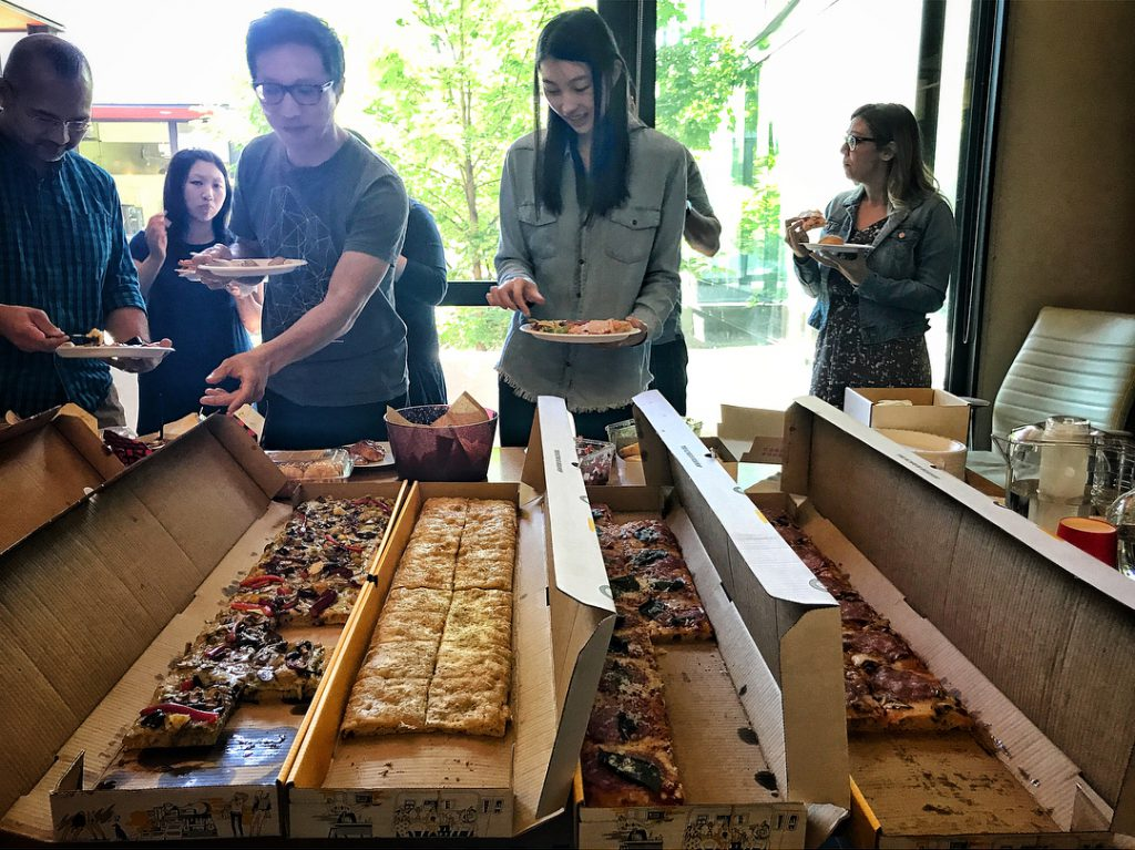 OXD team members lining up for a pizza lunch buffet