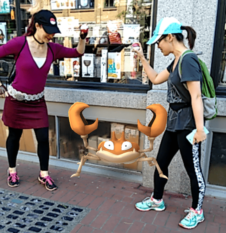 Two females holding Pokeballs playing PokemonGO, a kids entertainment game, on the sidewalk